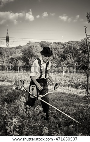 Old farmer using a petrol brush cutter to mow long grass and flowers. Black and white picture.