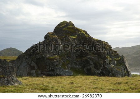 Old grass covered rock formation in the coast of Northern Norway.