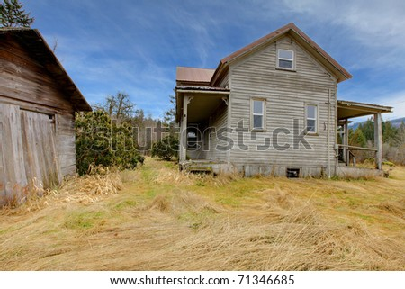 Old grey country farm house with winter Northwest landscape
