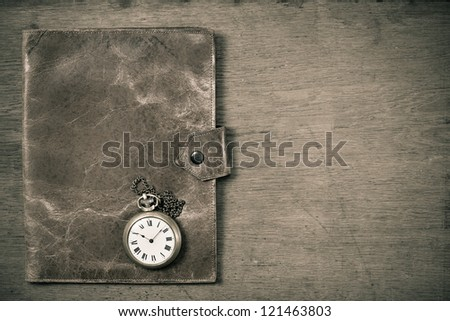 Old grunge leather notebook cover and pocket watch on grunge wooden table