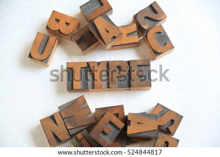 Old letterpress wood letters form the word type on white with other alphabet letters alongside