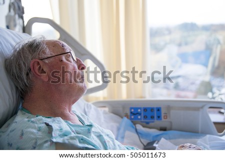 Old man in hospital bed looking up