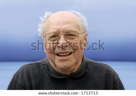 Old man laughing on a blue background