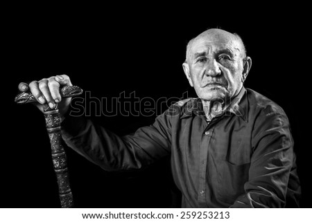 old man sitting with a stick