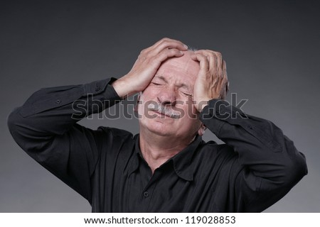 Old man with  headache on a grey background