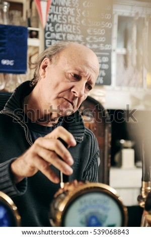 Old man working in a pub