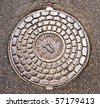 Old manhole cover in asphalt - stock photo