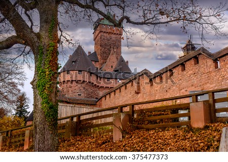 Old medieval castle of Haut-Koenigsbourg or fortress with towers viewed from below looking up an embankment with autumn leaves past a rustic wooden fence