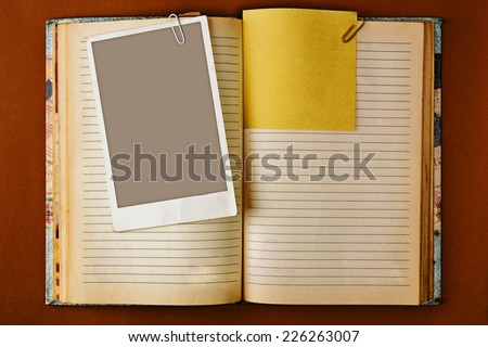 Old notebook with stained pages on brown paper surface. Useful for web site template design