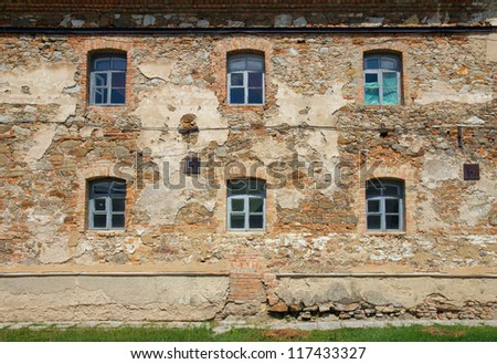 Old orange brick wall with six windows in Monastery - Fortress of Carmelites, Berdychiv, Zhytomyr Region, Ukraine