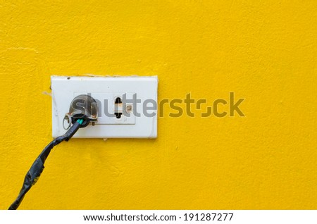 Old power plug on bright yellow wall.