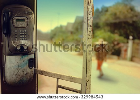 old public telephone booth with blur image of rural road