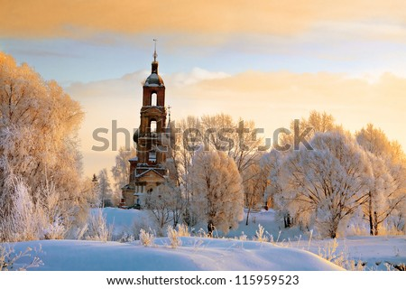 Old red church tilt with white trees on hill in Russian winter season