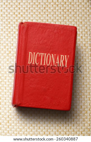 Old red dictionary in closeup on background
