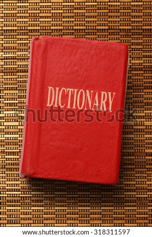 Old red dictionary on the textured background