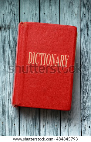 Old red dictionary on the wooden background