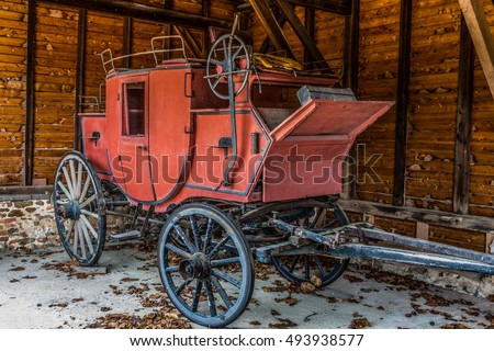 Old red stagecoach in a barn with leaves on the ground