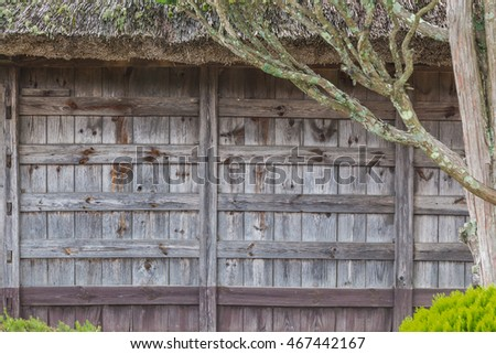 Old rustic Japanese house wood panel wall shown with small part of grass straw roof, good for background