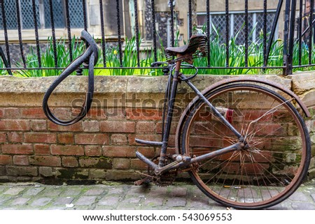 Old rusty bicycle cut in half, hooked to a grille with a chain in England
