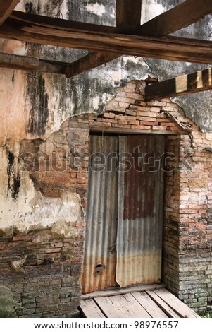 old rusty corrugated iron door of abandoned temple in Thailand