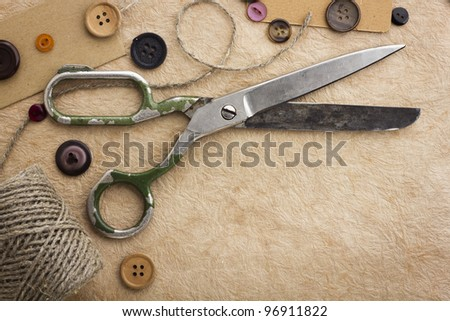 Old scissors and buttons on the paper texture