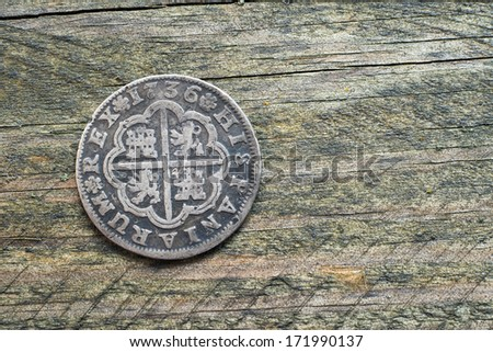 Old Spanish silver coin on wood