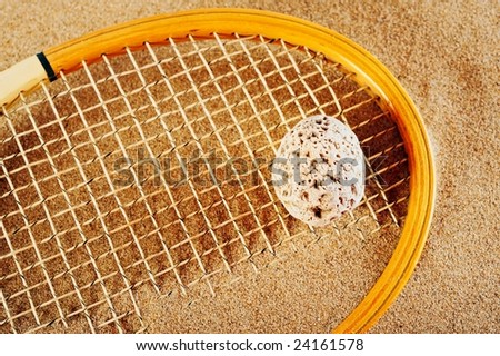 Old tennis racket on a beach in sand in the summer