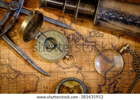 Old vintage retro compass and spyglass on ancient world map. Vintage still life. Travel geography navigation concept background.