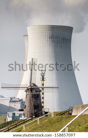 old windmill and nuclear power plant working together