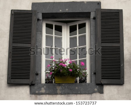 Old window with wooden shutters and flower box, Saint Jean Pied de Port, France
