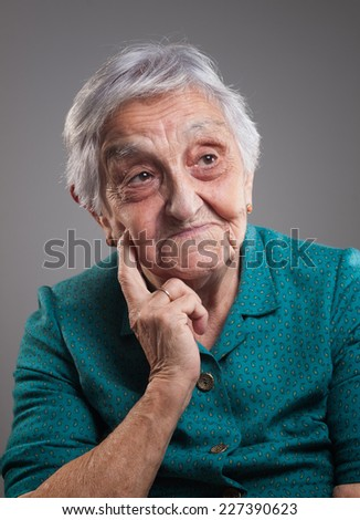 Old woman thinking. Elderly woman is isolated on dark background.