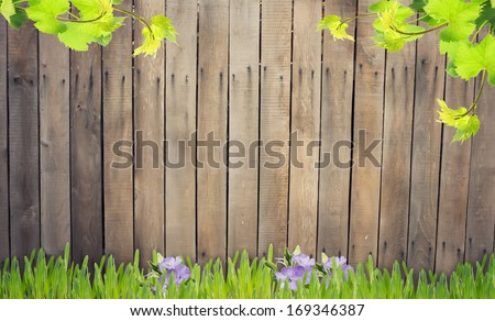 Old wooden brown fence. Grass and flowers against wooden background. Place for your text.
