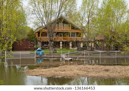 Old wooden house in the Russian tradition on the banks of the river in the village
