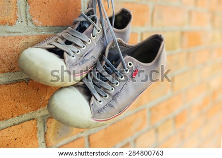 Old worn sneakers on brick wall