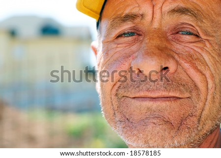 Old wrinkled man with yellow cap against blurry background