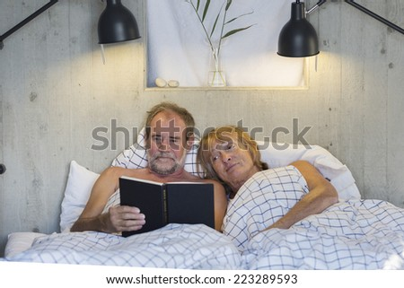 Older couple in bed reading a book
