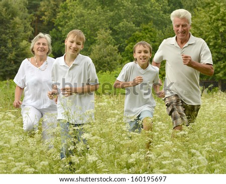 Older man and woman running with their grandchildren outdoors