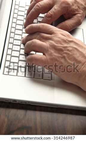 Older man's hands on his laptop keyboard with copy space