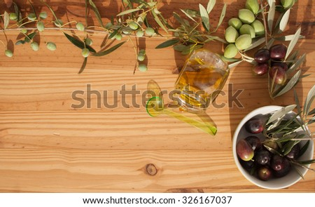 Olive branches on wood with Olive Oil