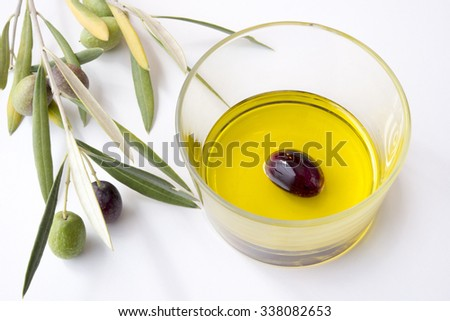 olive in a glass with oil and olive branches