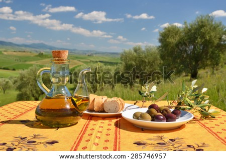 Olive oil, olives and bread on the wooden table against Tuscan landscape. Italy