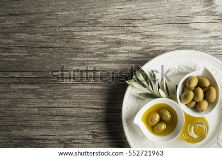 Olive oil with fresh olive fruits on wooden background
