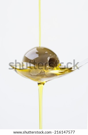 Olive on spoon with olive oil pouring over