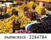 Olives and olive oil for sale at a market for farm products. - stock photo
