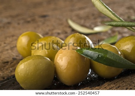 Olives marinated with olive oil on an old wooden table, closeup photo