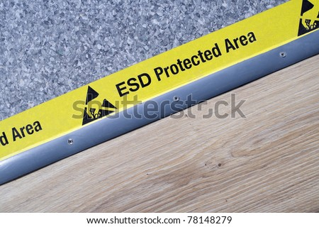 "On a floor of the scientific laboratory, covered industrial linoleum, pastes a yellow tape with a standard warning text: ""ESD Protected Area"""