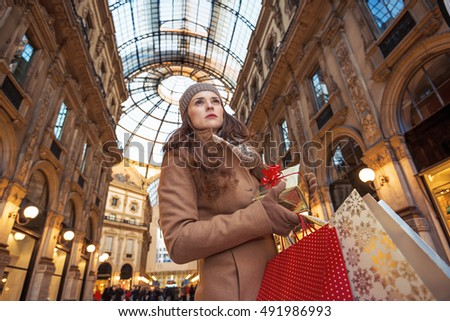 On a huge Christmas sales in Italian fashion capital. Portrait of elegant traveller woman with Christmas gift and shopping bags in Galleria Vittorio Emanuele II in Milan, Italy looking into distance