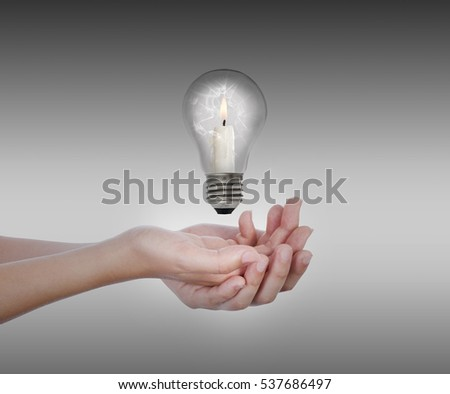 On hands levitates a broken bulb, inside there is a candle, with the flame lit, in front of a dark gray background