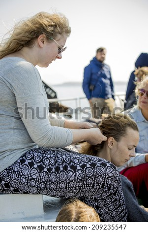 on the boat to Traena, Norway - July 09 2014: boat going to the Traenafestival, music festival taking place on the small island of Traena, lady braiding her friend's hair