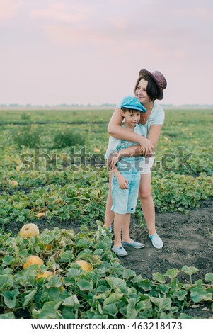 on the field with melons mother and son wearing a hat in the cap harvest